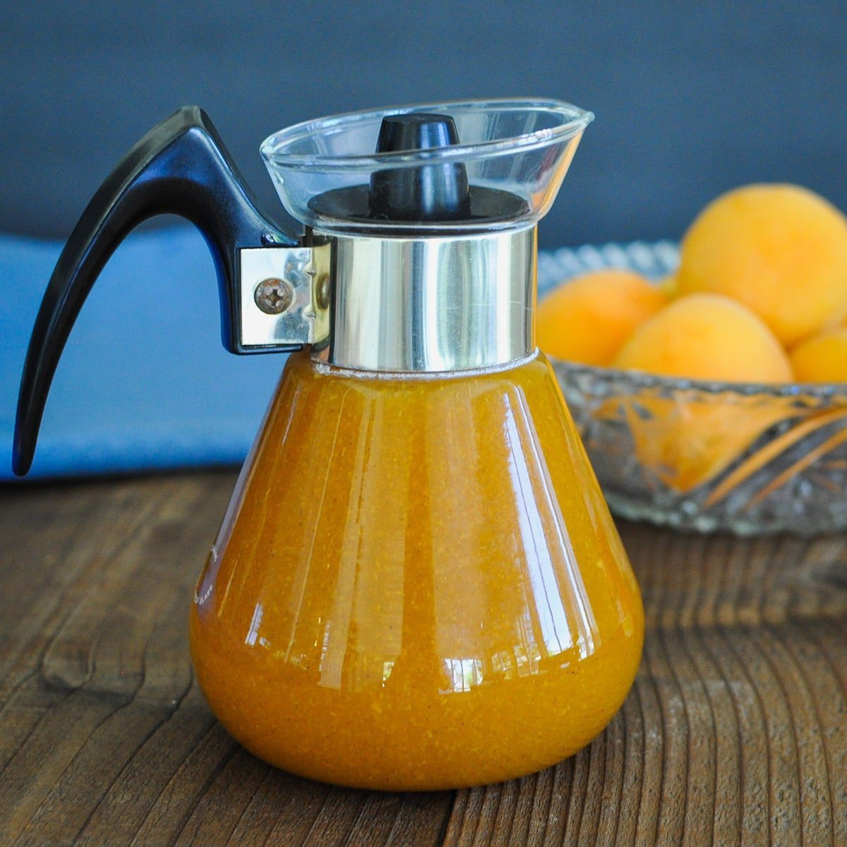 a dispenser of fresh made syrup in front of a bowl of apricots