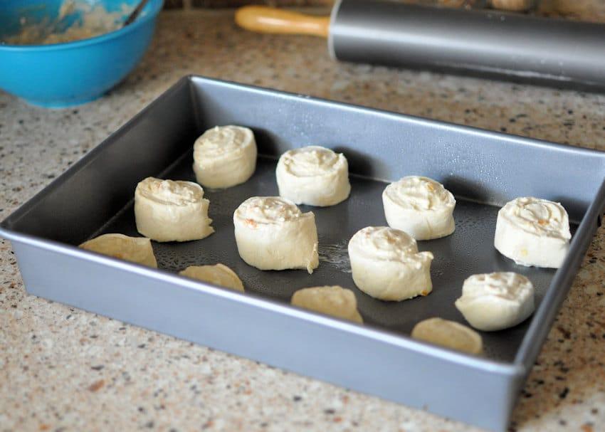 Orange Cream Cheese Cinnamon Roll in a pan ready to rise