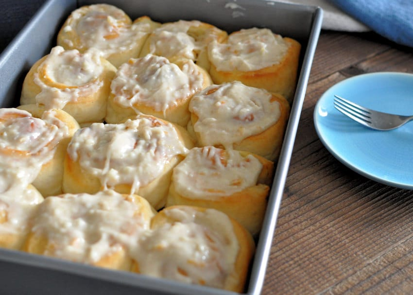 Orange Cream Cheese Cinnamon Rolls topped with frosting and ready to eay