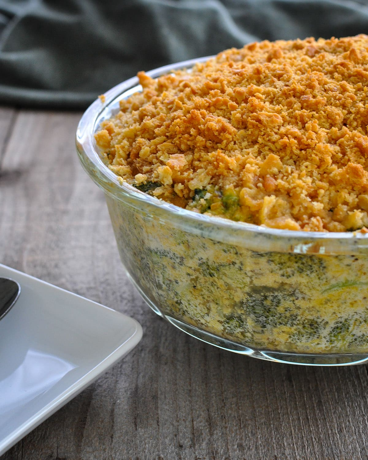 broccoli cheese casserole in a clear dish next to a white plate