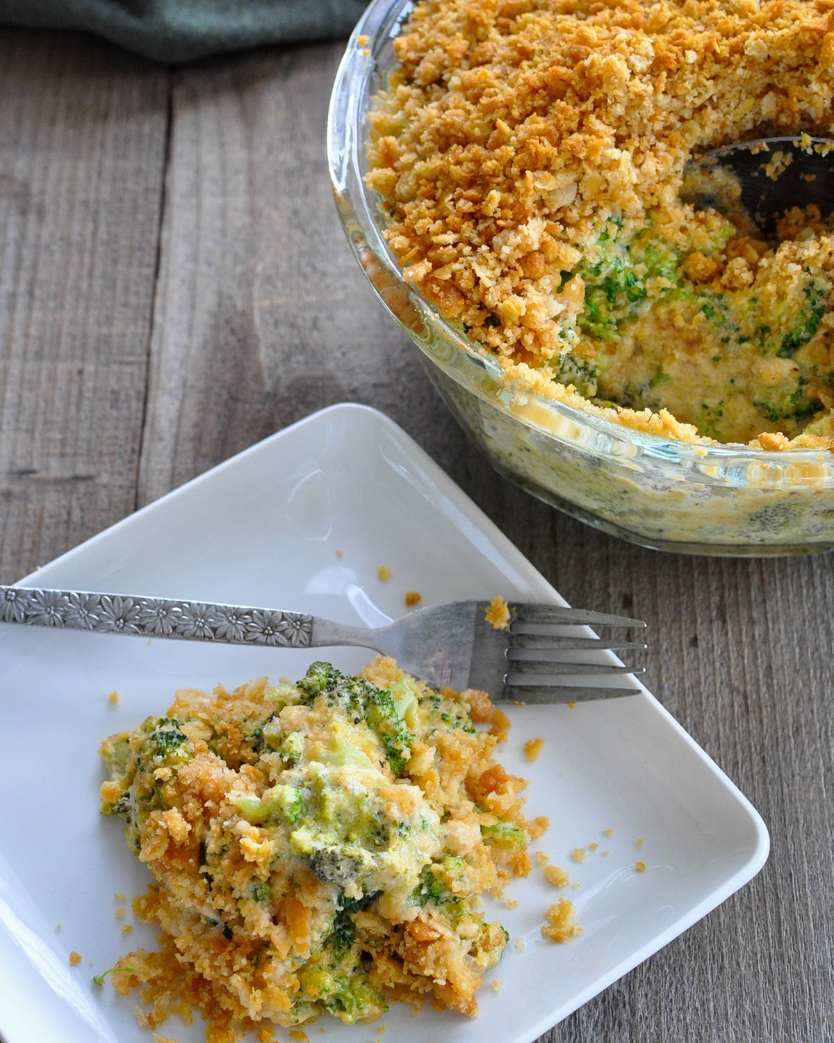 sour cream and cheese broccoli casserole on a white plate with a fork