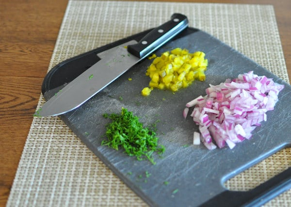 chopped pickles, onions and parsley on a black cutting board