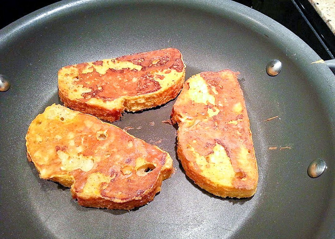 3 slices of pumpkin french toast cooking in a skillet