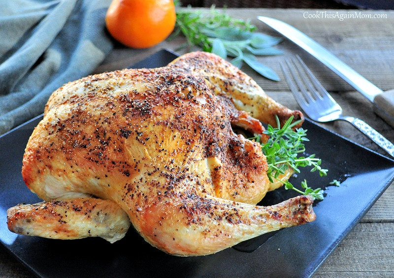 Roasted Whole Chicken with herbs sitting on a black platter