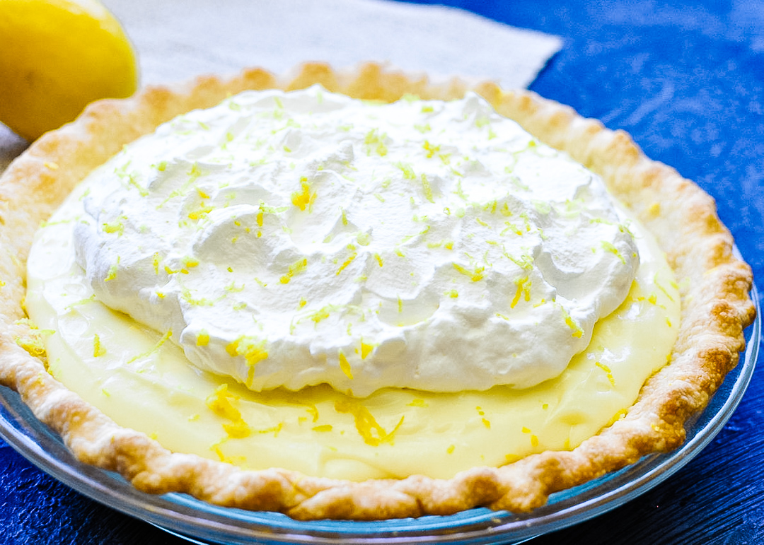 lemon pie topped with whipped cream setting on a blue background