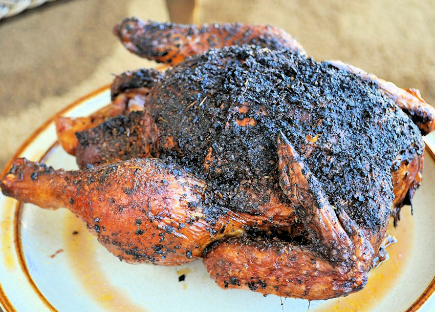 a slightly charred, whole chicken that has been cooked on a bbq