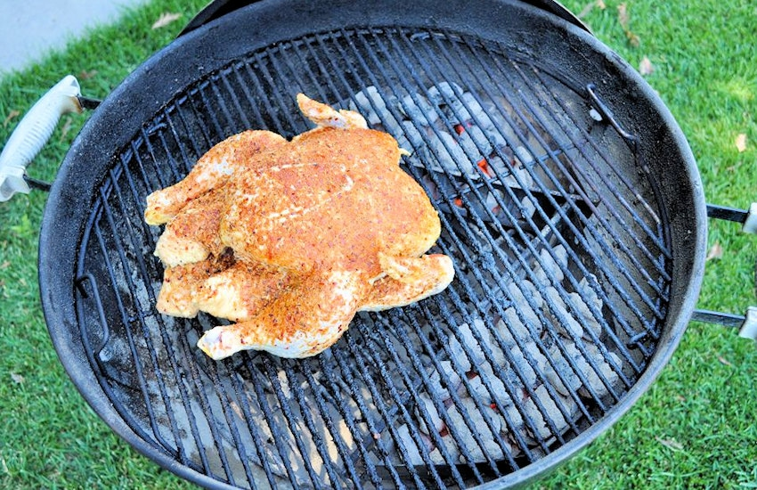 a raw chicken coated in seasoning starting to cook on a weber bbq
