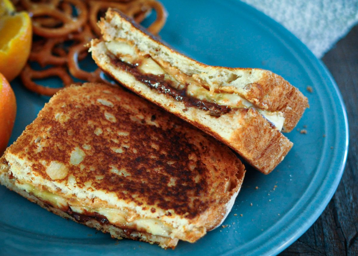 a grilled sandwich with peanut butter, Nutella, and banana sitting on a blue plate next to pretzels and an orange.