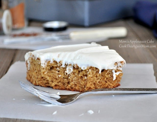 frosted applesauce cake sitting on a piece of parchment paper next to a fork