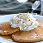 pancakes on a white plate topped with whipped cream