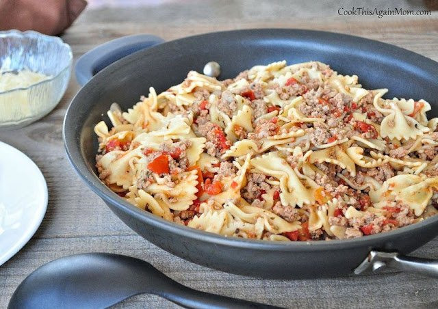 turkey sausage with pasta and tomato in a black skillet