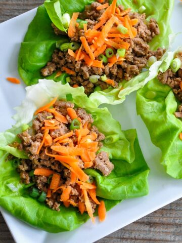 ground meat sitting in a lettuce cup with shredded carrots