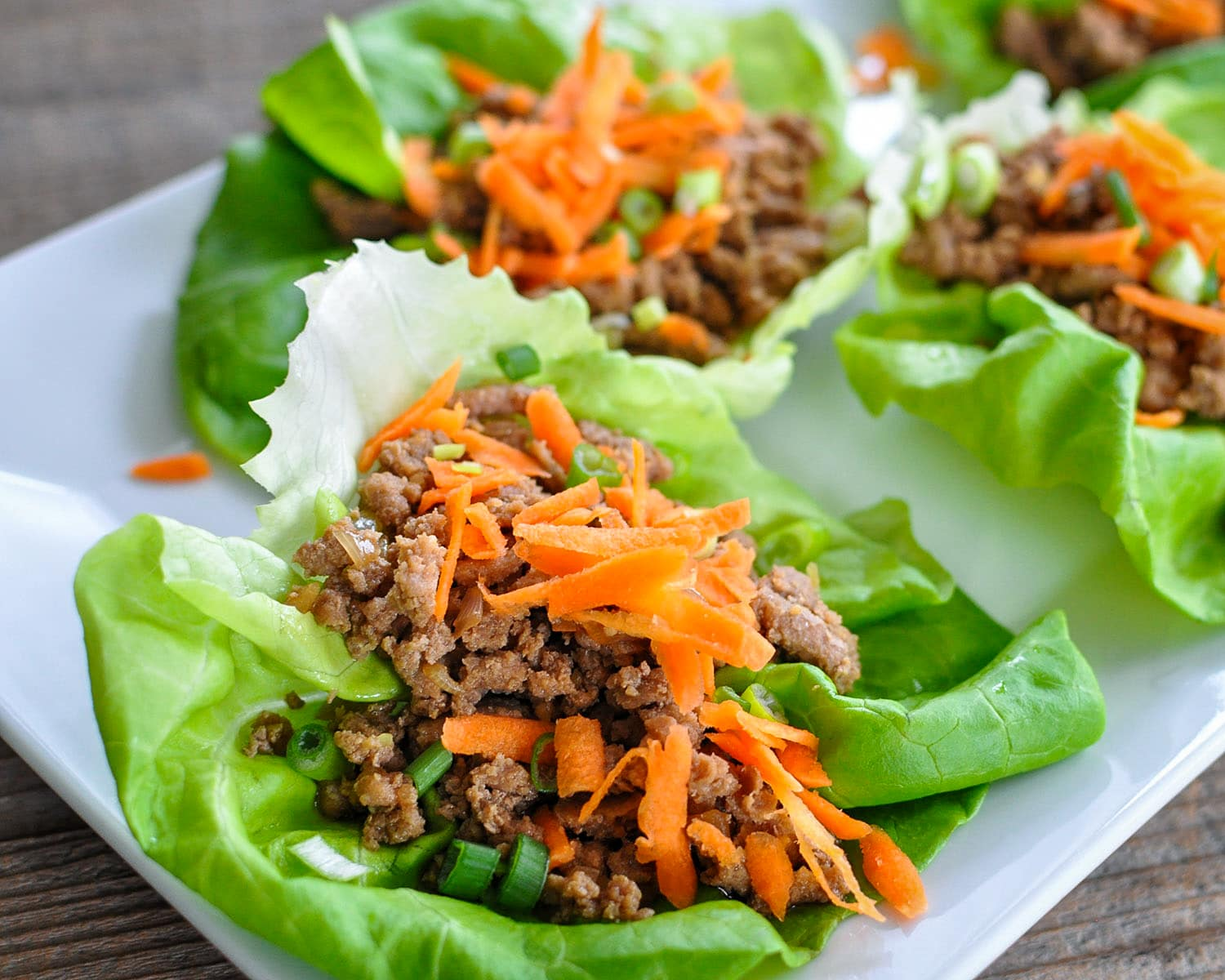 ground turkey with spices sitting in a lettuce bed with carrots