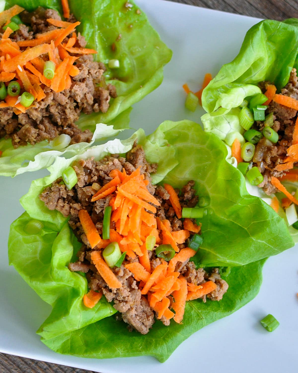 ginger and garlic spiced ground meat in a lettuce cup topped with carrots
