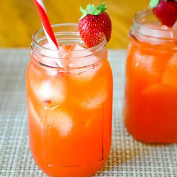 strawberry lemonade in a mason jar glass with ice and a red and white straw