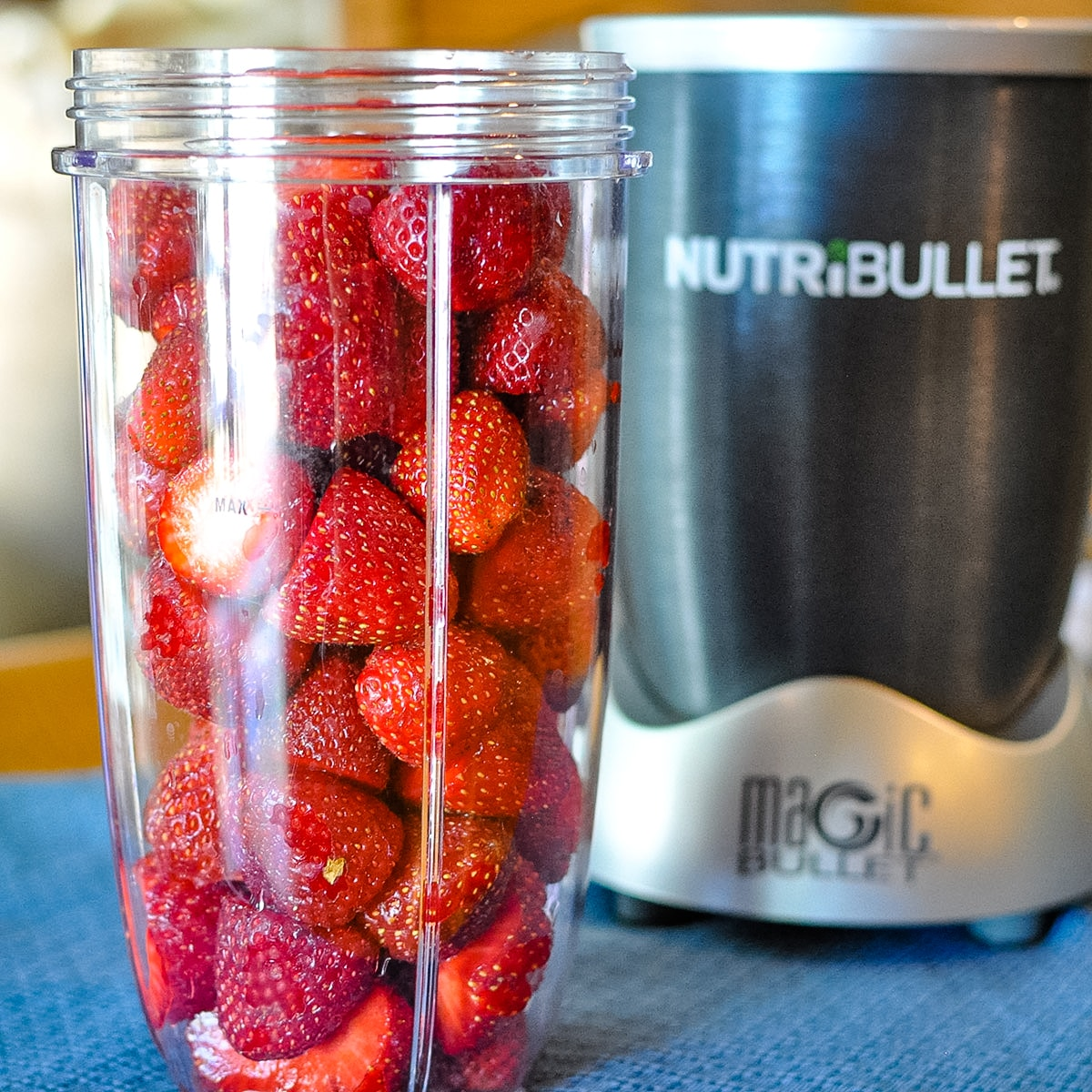 a nutri bullet canister full of fresh strawberries before being pureed