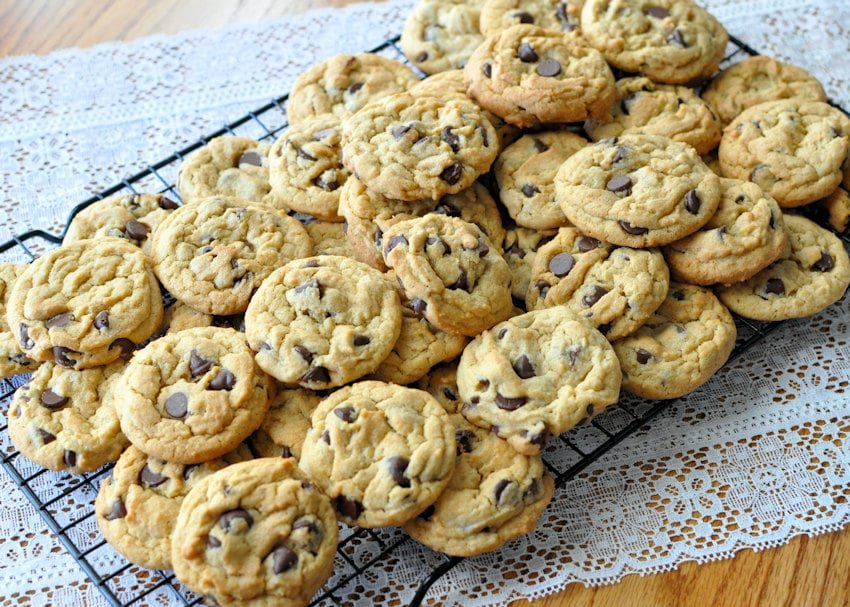 a few dozen chocolate chip cookies on a black wire rack sitting on white lace