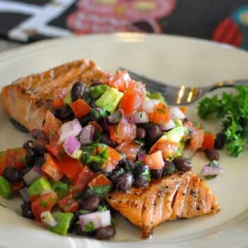 salmon filet covered with black bean salsa on a cream colored plate