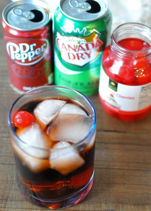 Dr. Pepper in a glass with ice next to soda cans and cherries in a jar