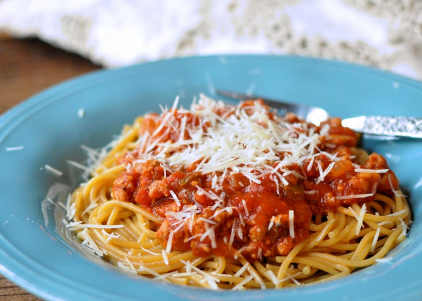 sauce covered spaghetti in a blue bowl