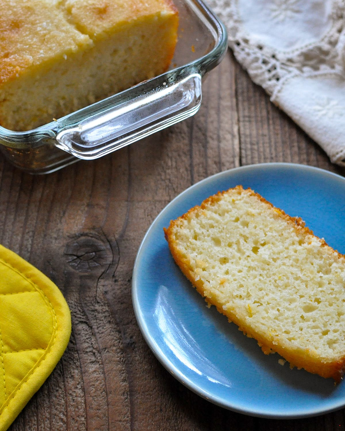 a slice of lemon bread on a blue plate next to the loaf of lemon bread in a glass baking dish