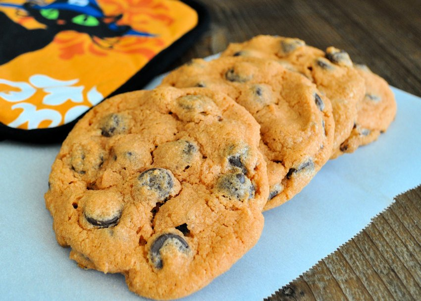 orange chocolate chip cookies on a piece of parchment paper