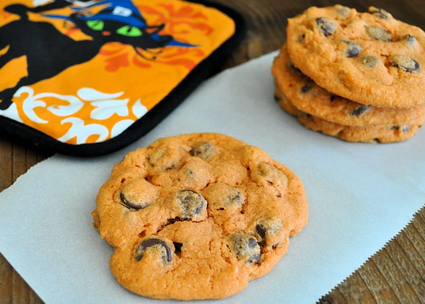orange colored chocolate chip cookies on a piece of parchment papaer