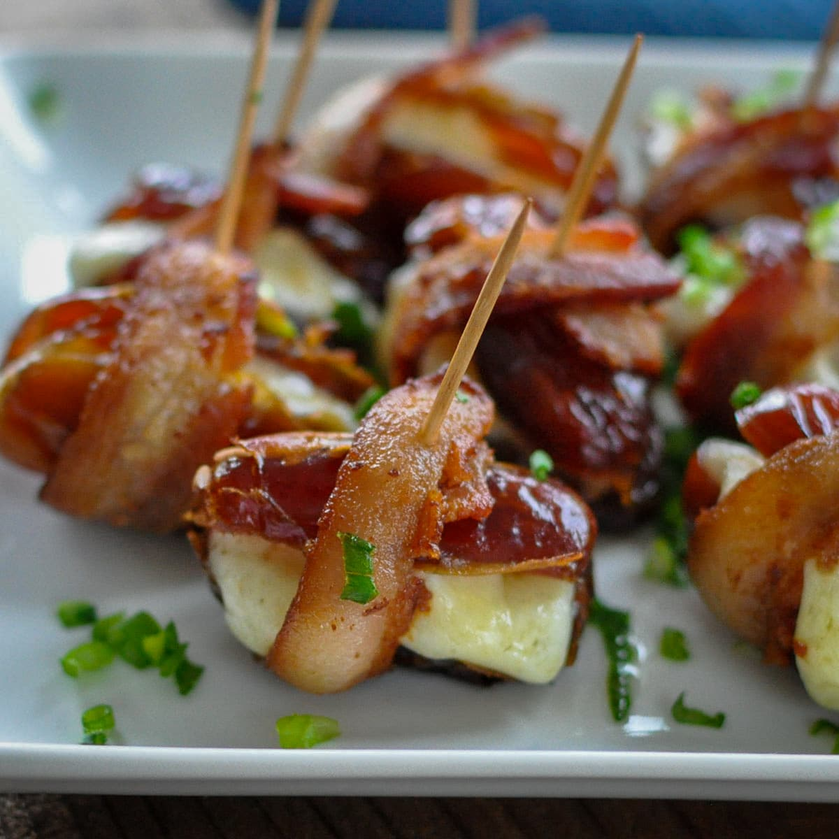 dates stuffed with cheese wrapped in bacon on a plate