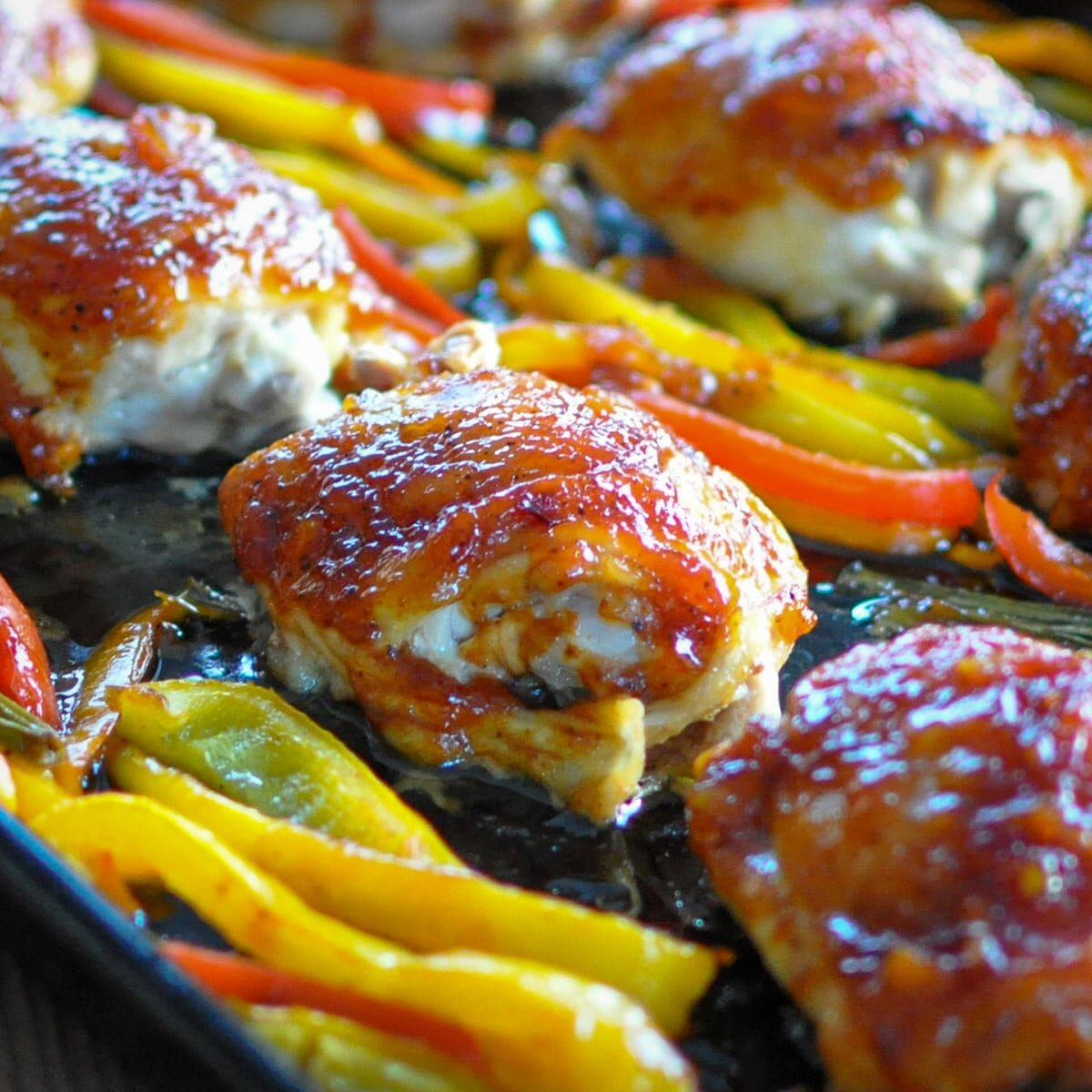 baked chicken thighs with peppers on a cookie sheet