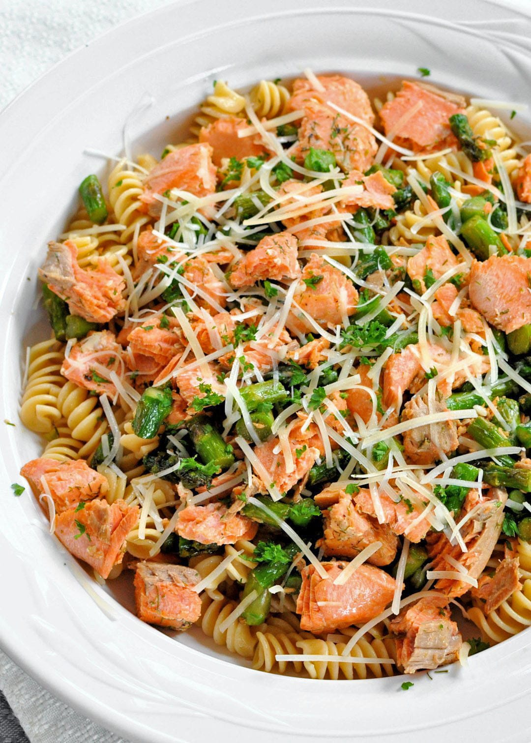 white bowl filled with spiral pasta, salmon and asparagus