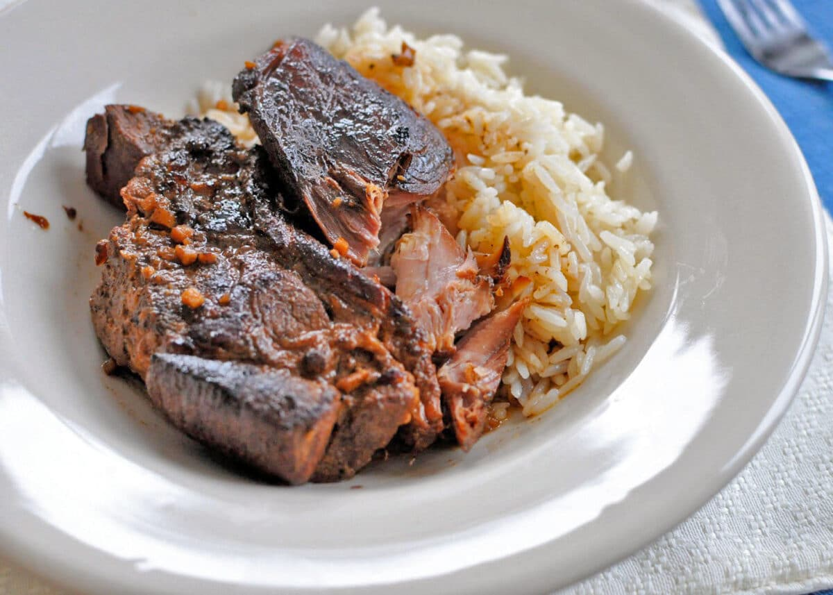 Overhead shot of Asian Country-Style Pork Ribs with rice in a white bowl. cooked in the slow cooker.