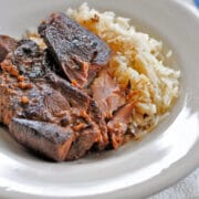 pork ribs in a white bowl with a side of rice