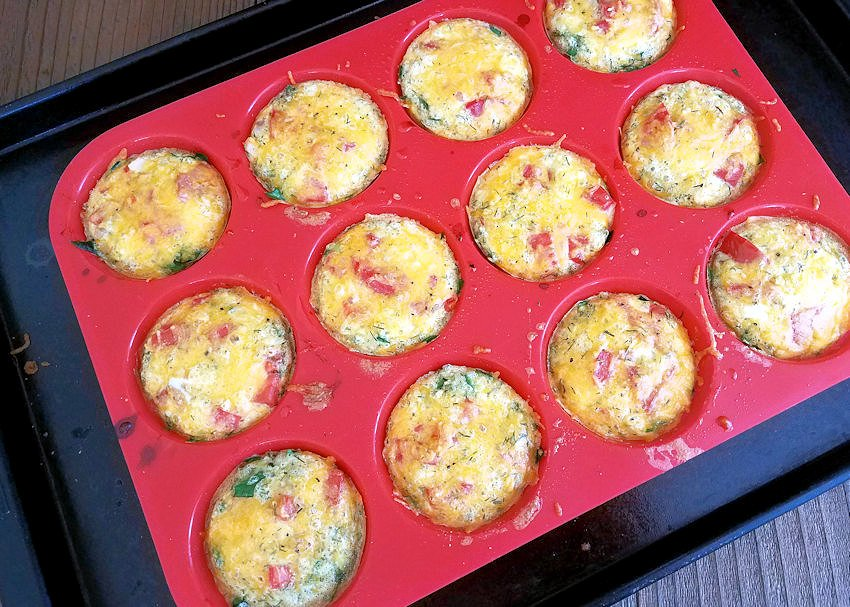 just baked egg cups in a red muffin tray