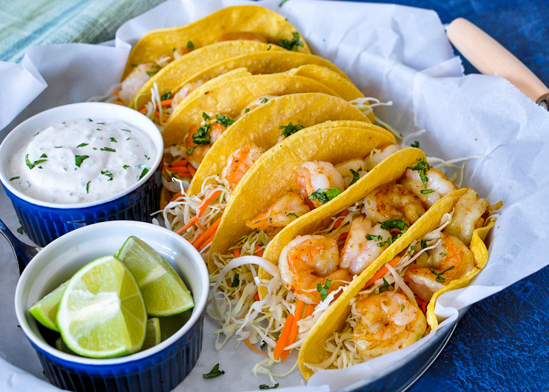 Shrimp tacos on a tray with side dishes of sour cream sauce and cut up limes