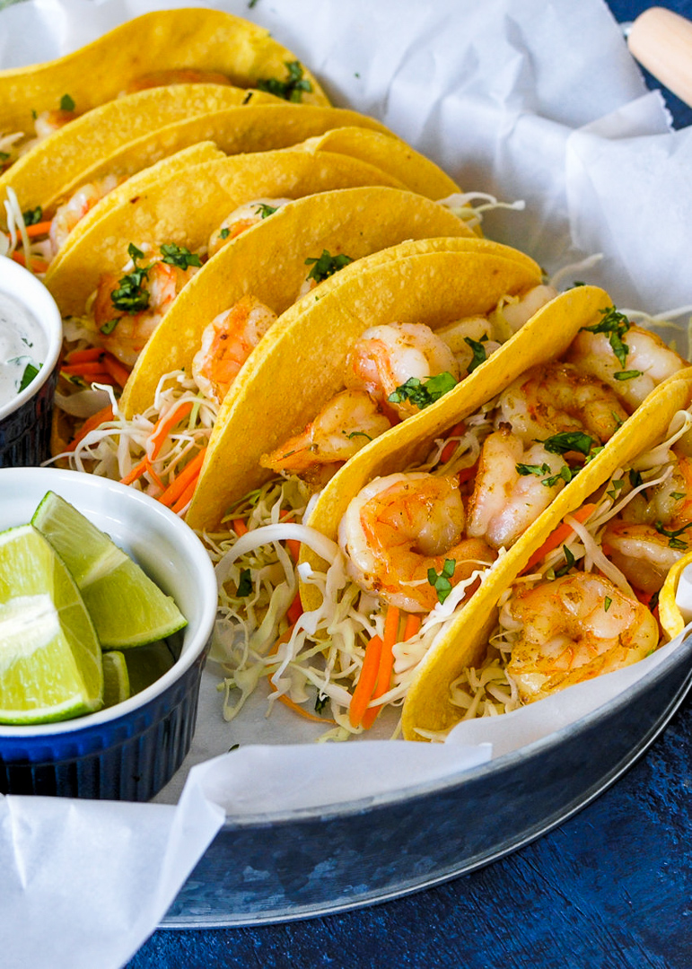a close up of shrimp tacos with cabbage, carrots and cilantro