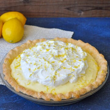 a whole lemon cream pie next to lemons on a blue background
