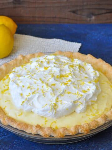 a whole lemon cream pie next to lemons on a blue background