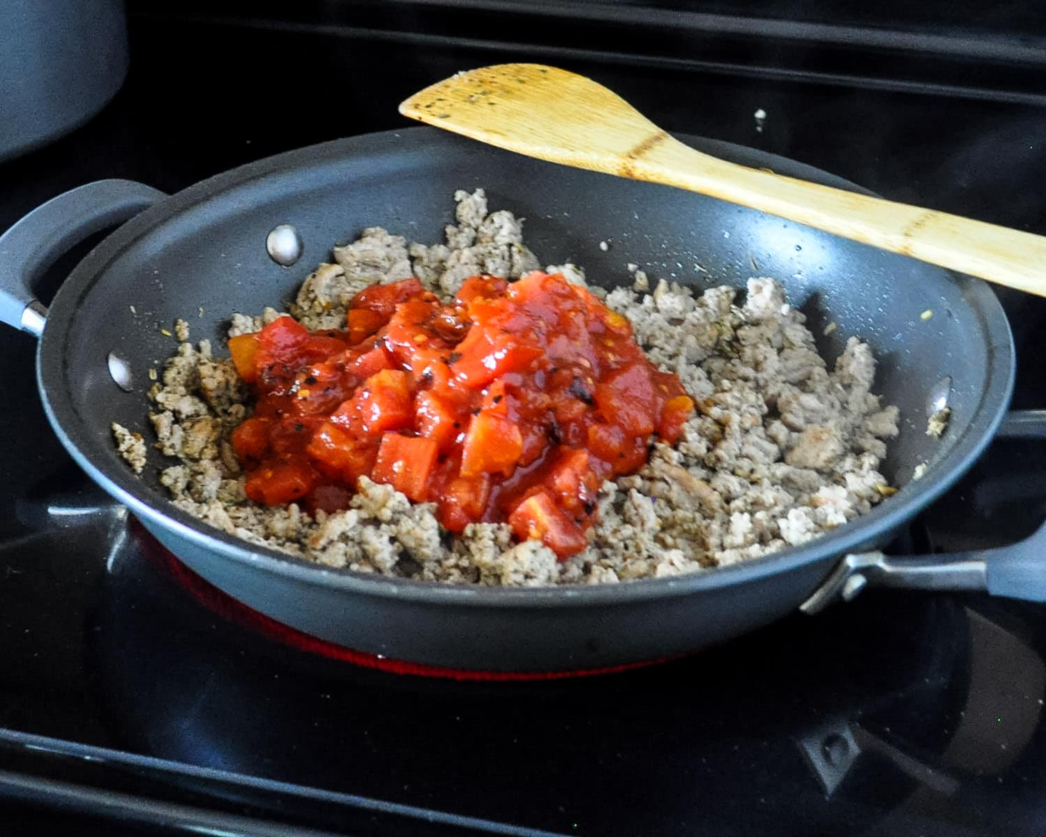 ground turkey and spices with tomatoes cooking in a skillet