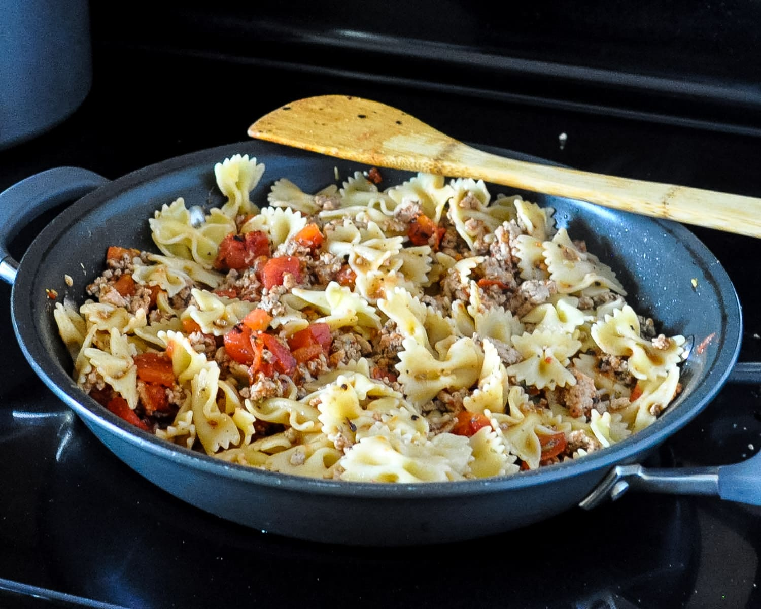 ground turkey and spices with tomatoes and pasta cooking in a skillet