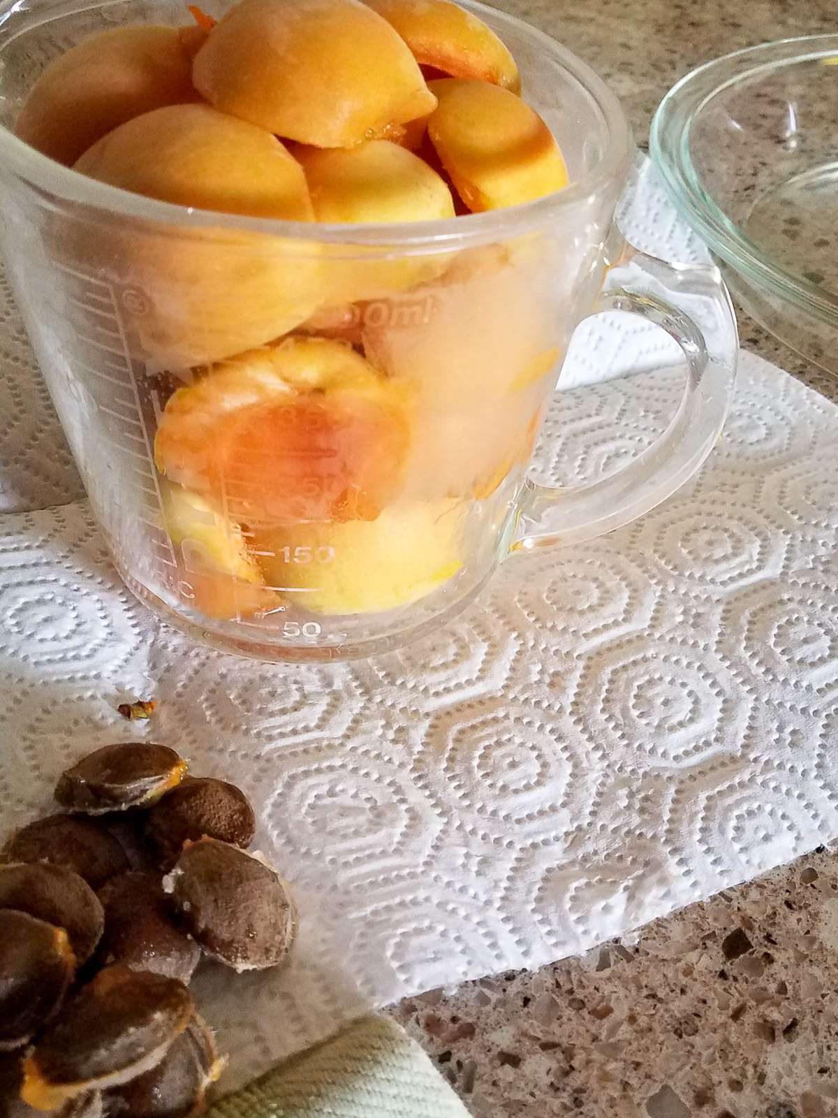 apricot halves being put in a glass measuring cup