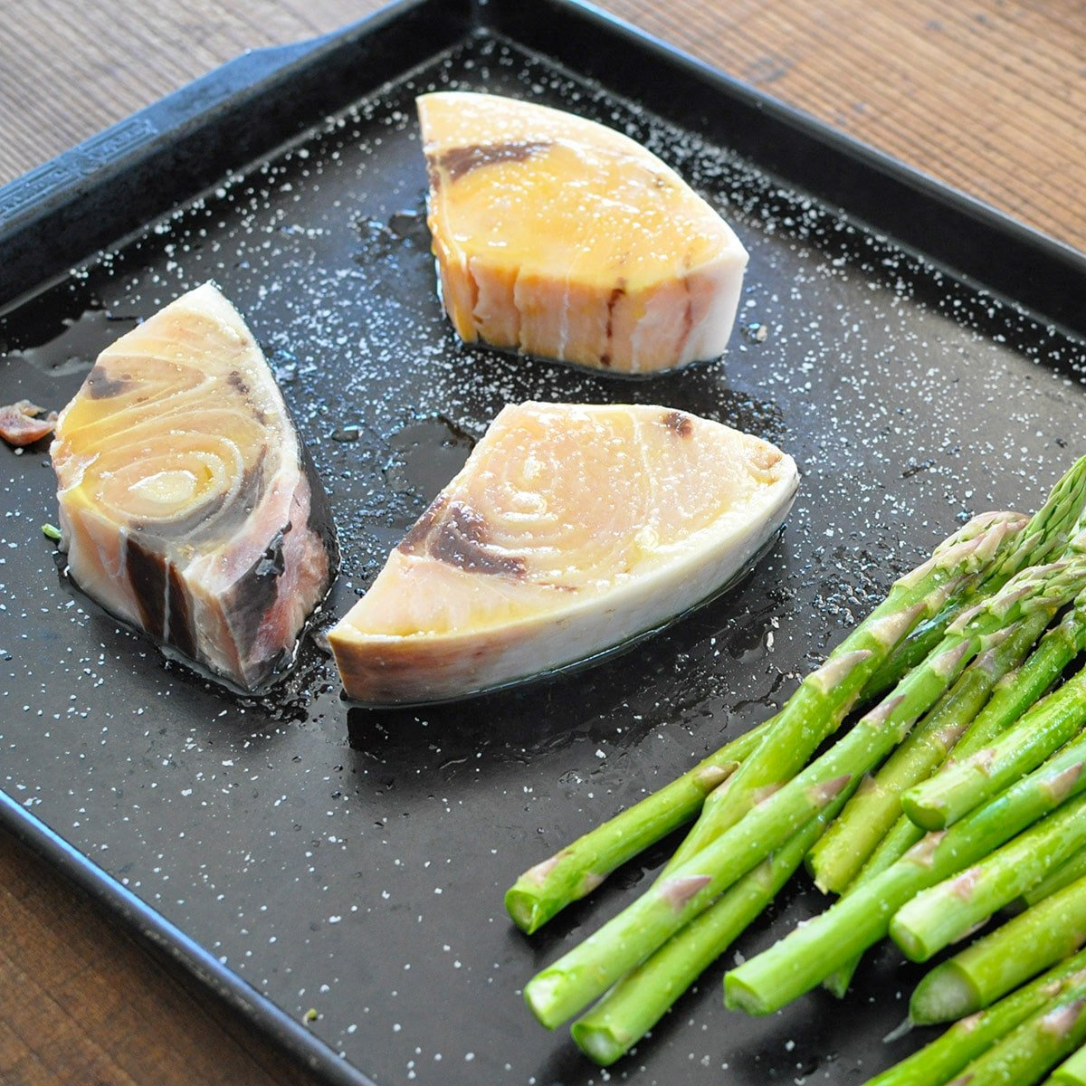 swordfish steaks and asparagus on a dark baking sheet