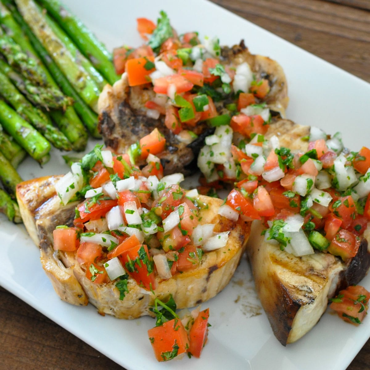 pico de gallo over grilled swordfish steaks next to asparagus