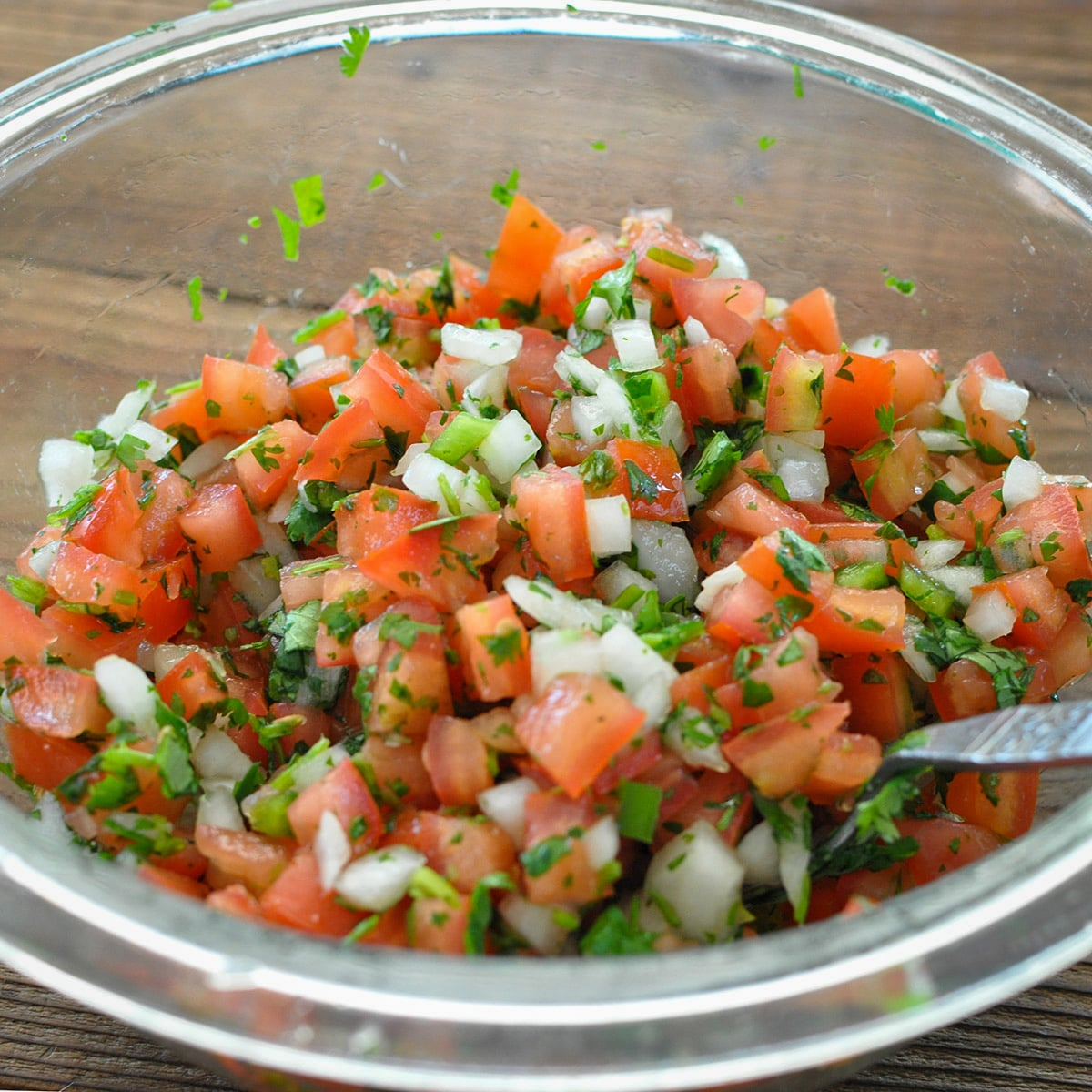a glass bowl filled with pico de gallo