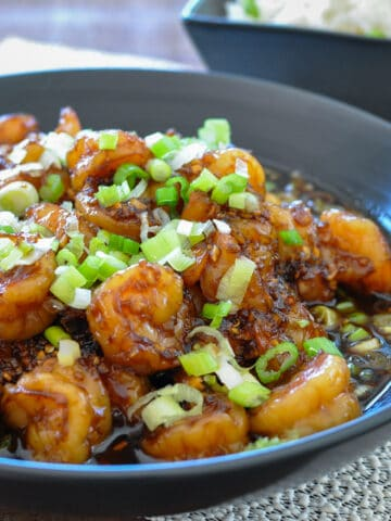 shrimp with a sweet garlic sauce in a black bowl topped with green onions