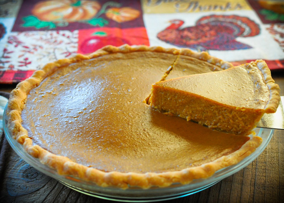 a whole butternut squash pie with a single slice being removed