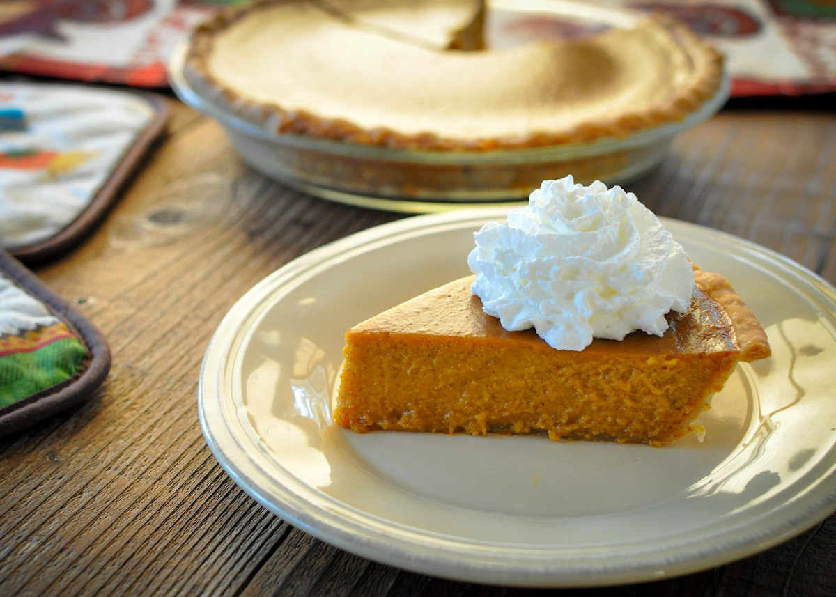 a slice of butternut squash pie with whipped cream on a cream colored plate