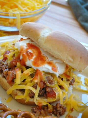 taco meat with salsa, cheese, and sour cream on a bun