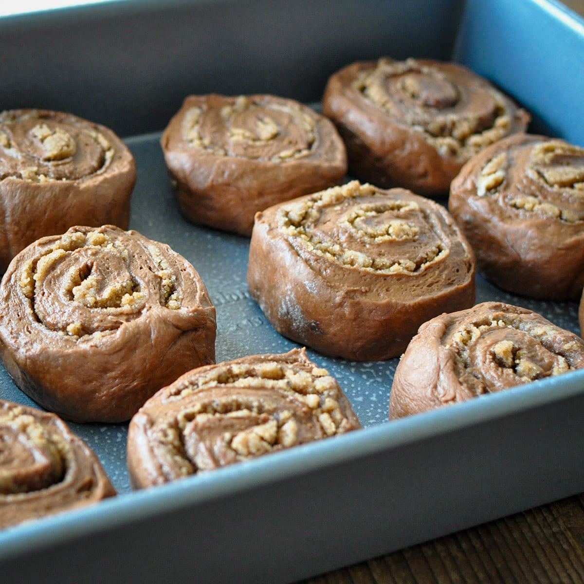 raw cinnamon rolls in a baking sheet ready to rise