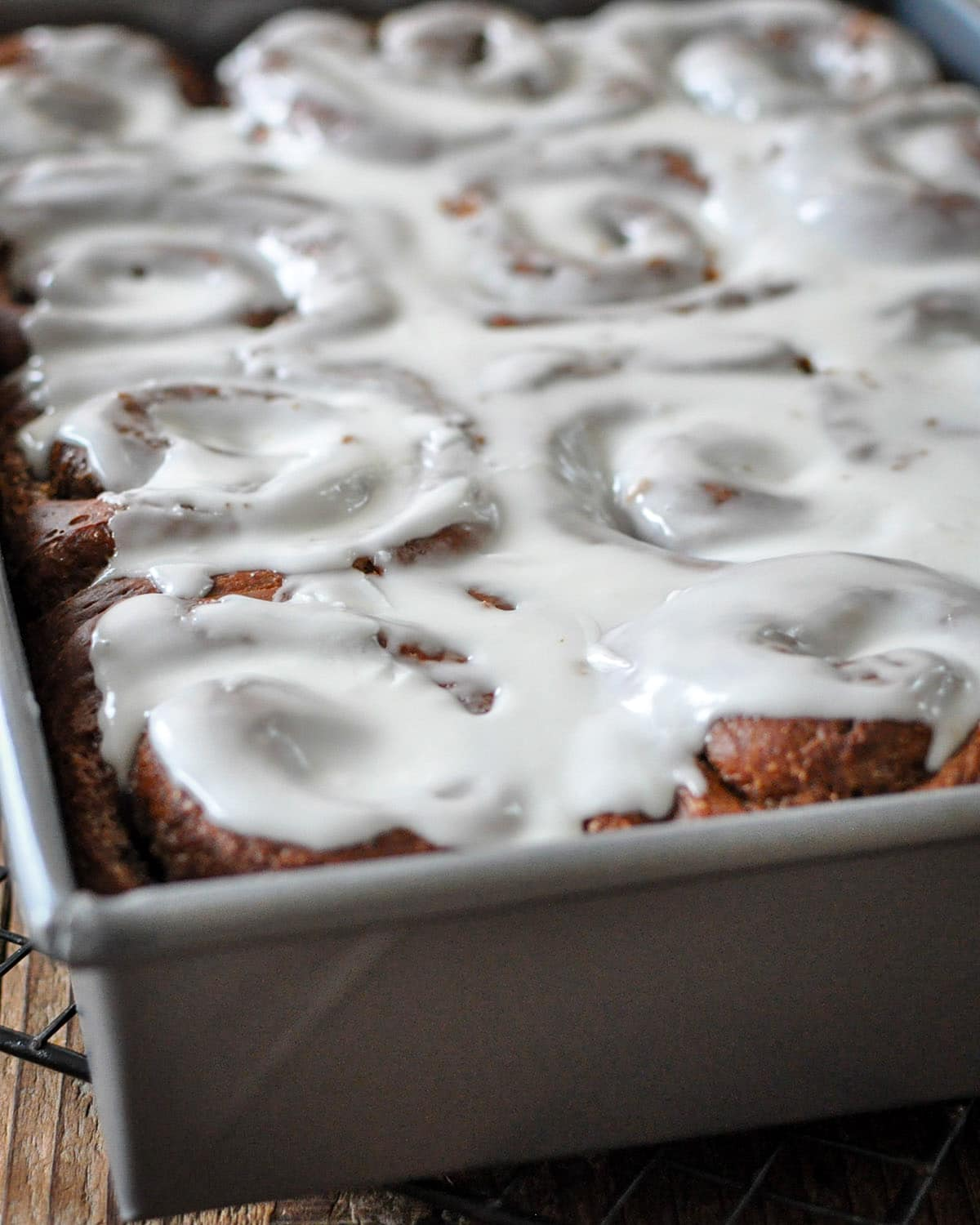 a baking pan filled with frosted chocolate cinnamon rolls