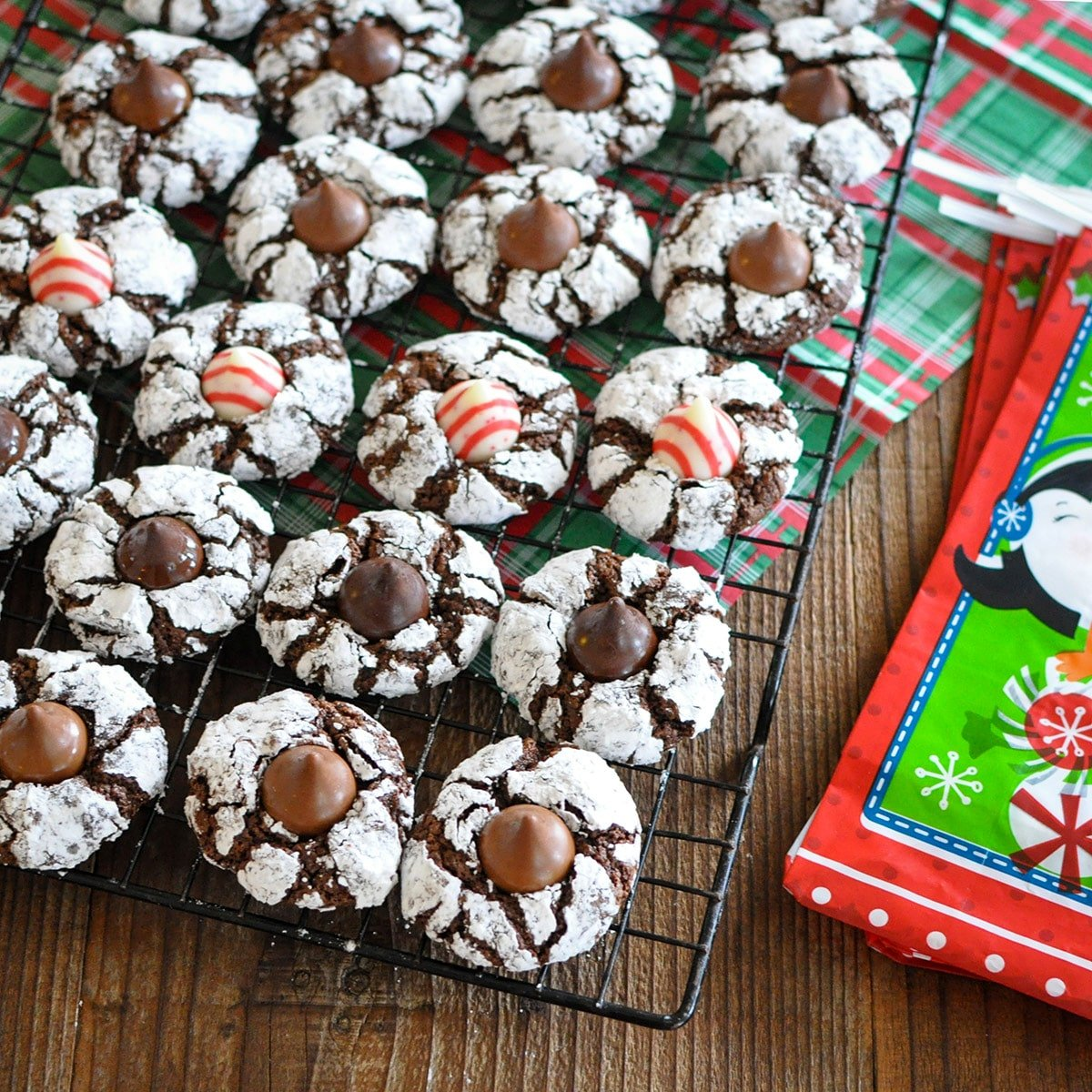 chocolate crinkle cookies with a holiday hershey kiss in the middle on a black rack